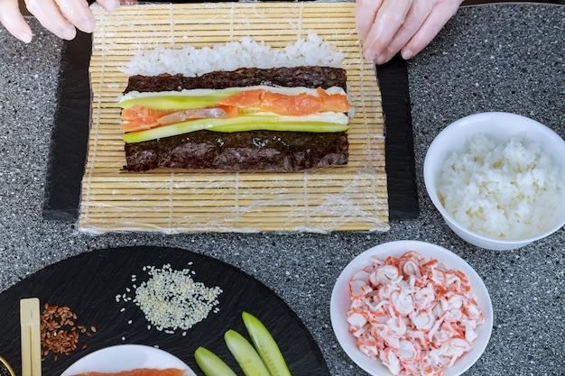 Ręce szefa kuchni robią japońską roladę sushi z łososiem