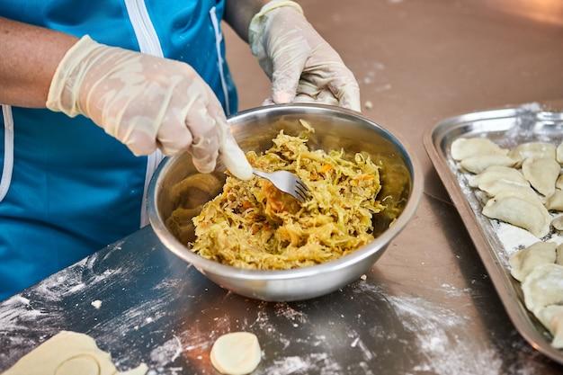 Ręce szefa kuchni rzeźbią pierogi z duszoną kapustą. pyszne domowe jedzenie.
