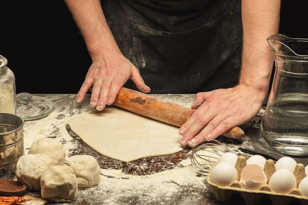 Ręce szefa kuchni toczą ciasto na drewnianym stole z mąką pszenną