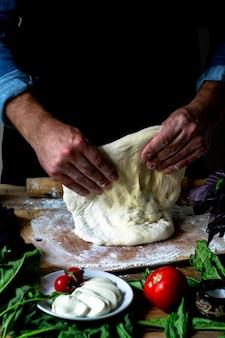 Ręce szefa kuchni włoski szef kuchni gotowanie pizzy człowiek ręce gotowanie ciasta na pizzę na pizzę gotuje ręce