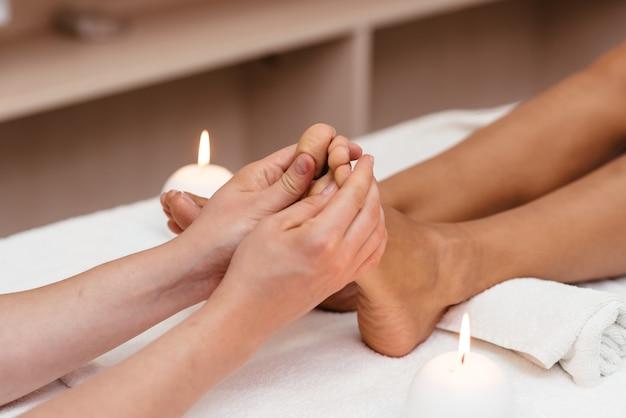Ręce terapeuty w rękawicach ochronnych masujących stopy kobiety.