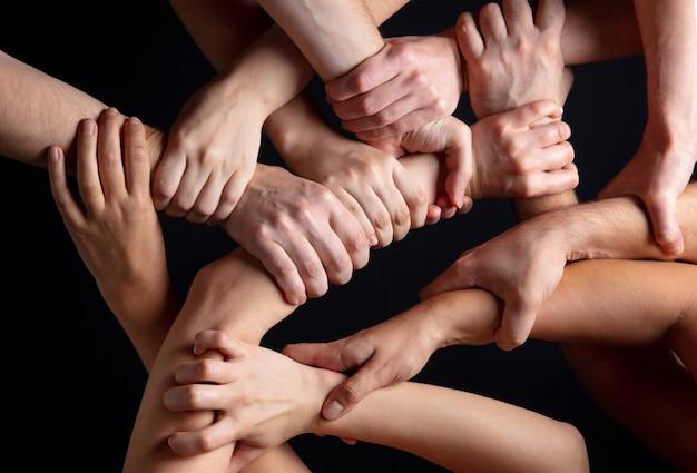 Ręce tłumu narodów w kontakcie na białym tle na tle czarnego studia koncepcja relacji międzyludzkich