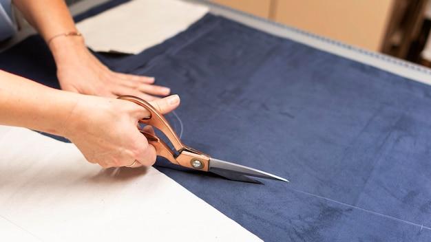 Ręce tnące materiał nożyczkami z bliska