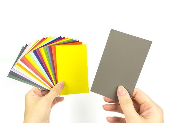 Ręce trzyma acolor paletę farb na białym tle. próbki farb z karty kolorów.