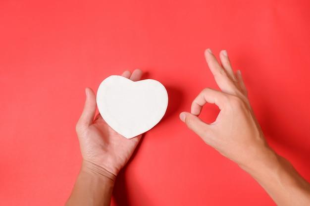 """Ręce trzyma białe pudełko w kształcie serca i ręcznie wykonane jako symbol """"ok"""" na czerwonym tle. walentynki pudełko."""