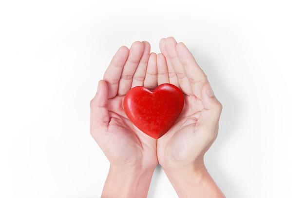 Ręce trzyma czerwone serce, zdrowie serca i darowizny pojęcia