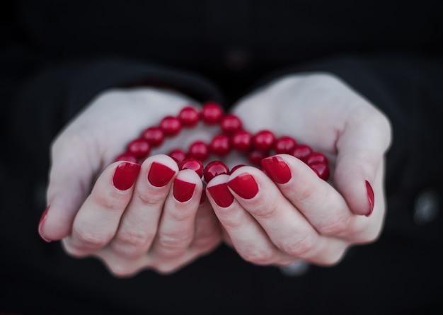 Ręce trzyma czerwony różaniec