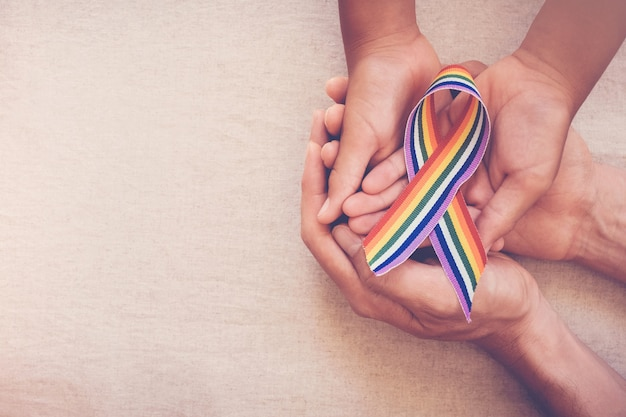 Ręce trzyma gejowskiej tęczy wstążka dla świadomości lgbt