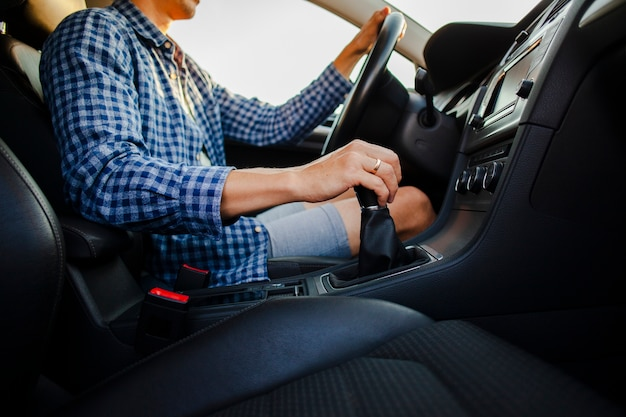 Ręce trzyma koło samochodu i drążek zmiany biegów