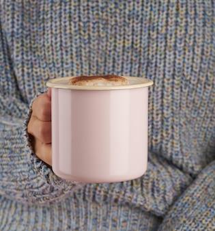 Ręce trzyma kubek gorącej czekolady, szary przytulny sweter, piękny różowy manicure, styl domowy