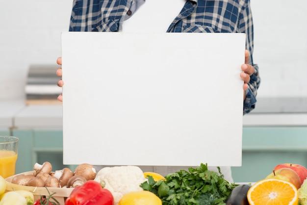 Ręce trzyma makiety znak obok warzyw