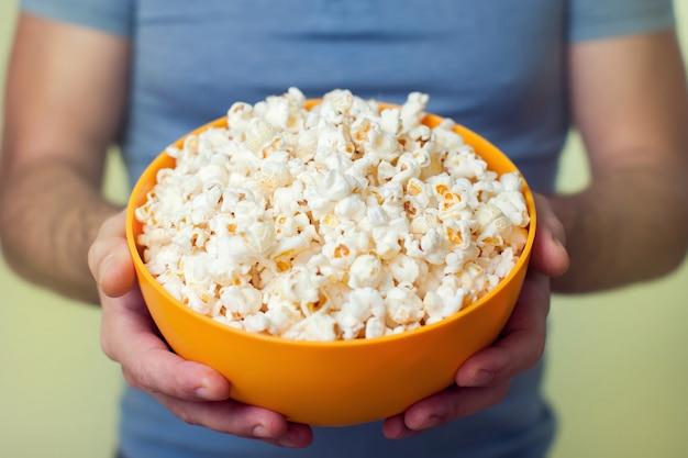 Ręce trzyma miskę popcornu