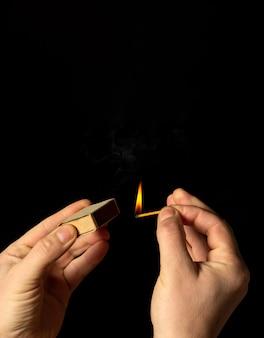 Ręce trzyma płonącą zapałkę na czarnym tle