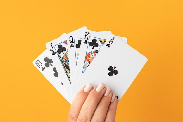 Ręce trzyma poker królewski na żółtym tle