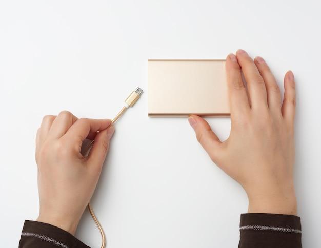 Ręce trzyma przenośny power bank i złoty kabel na białej powierzchni