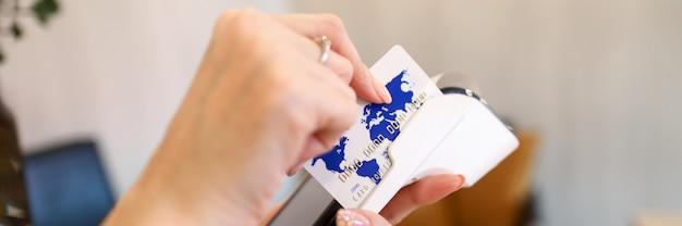 Ręce trzyma przenośny terminal do płatności kartą. dostawcy usług płatniczych. możliwość przyjmowania kart kredytowych przez internet. posiadacz karty płaci za zakupy w witrynach sklepów i usług internetowych podczas kwarantanny