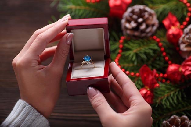 Ręce trzyma pudełko z pierścieniem z niebieskim kamieniem