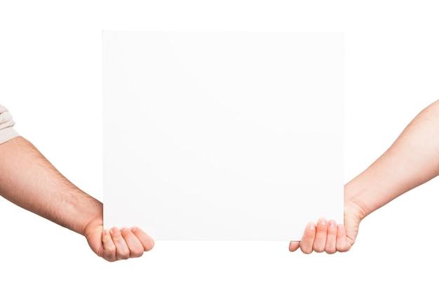 Ręce trzyma pustą białą deskę. na białym tle