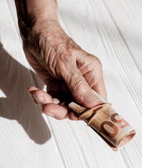 Ręce trzyma rolkę banknotów