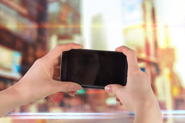Ręce trzyma telefon komórkowy, aby zrobić zdjęcie