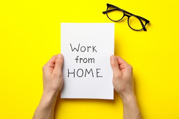 Ręce trzymać arkusz z pracy w domu na żółtej powierzchni w okularach