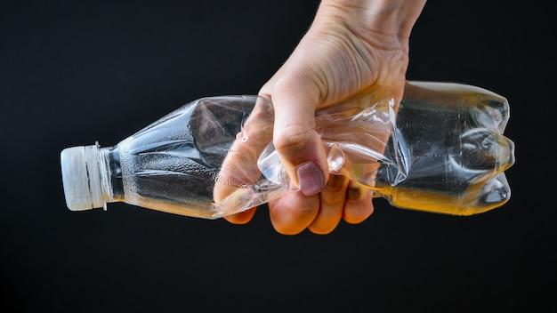 Ręce trzymaj plastikowe butelki, aby je wyrzucić jako koncepcję globalnego ocieplenia