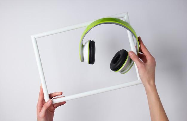 Ręce trzymają białą ramkę ze słuchawkami stereo na białej powierzchni