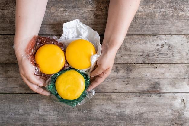 Ręce trzymają całe sery holenderskie i holenderski ser kozi z holandii na rustykalnym drewnianym stole, widok z góry.