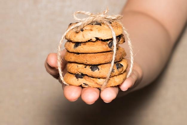 Ręce trzymają czekoladowe ciasteczka ciasteczka z kawałkami czekolady związane wstążką.