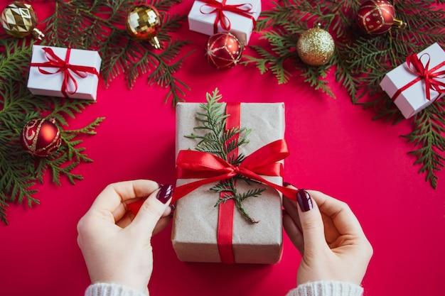 Ręce trzymają piękne pudełko z kokardą na czerwonym stole. koncepcja bożego narodzenia.