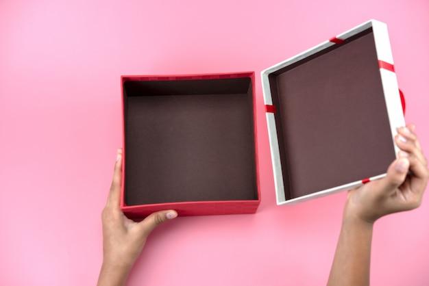 Ręce trzymają puste czerwono-białe pudełko upominkowe