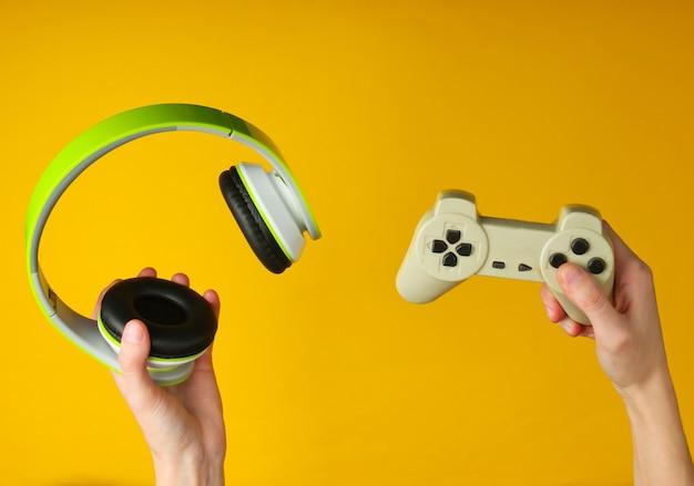Ręce trzymają słuchawki stereo i gamepad na żółtej powierzchni