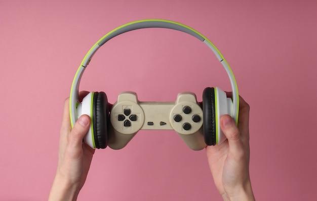 Ręce trzymają słuchawki stereo i gamepada na różowej, pastelowej powierzchni