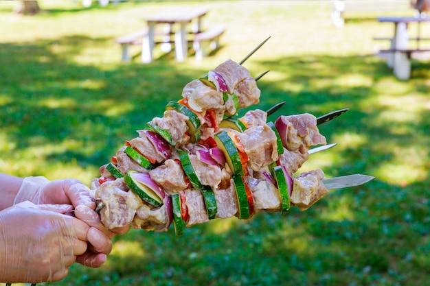 Ręce trzymają szaszłyk zrobiony z wieprzowiny i warzyw na metalowych szaszłykach.