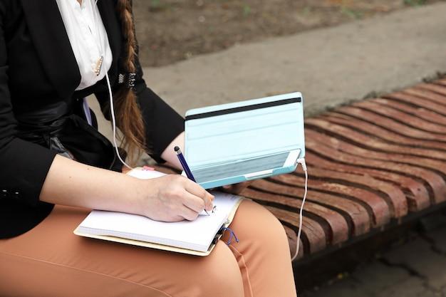 Ręce trzymają tablet i notatnik, na którym robi notatki