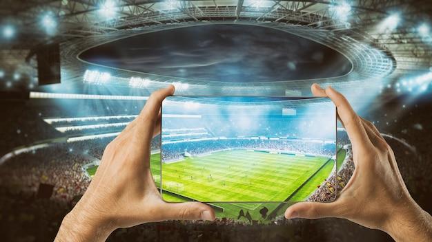Ręce trzymają telefon komórkowy z stadionem piłkarskim