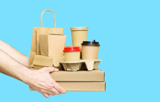 Ręce, trzymając asortyment pojemników dostawy żywności na białym tle na niebieskim tle. dostawa jedzenia