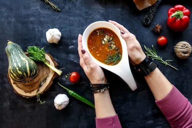 Ręce trzymając biały talerz z zupą jarzynową z nasionami