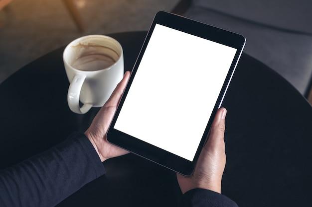 Ręce trzymając czarny tablet pc z biały pusty ekran i filiżankę kawy na tle tabeli