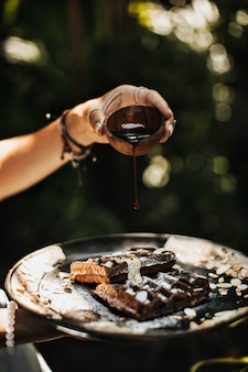 Ręce trzymając czarny talerz z goframi, orzeszkami ziemnymi i sosem czekoladowym