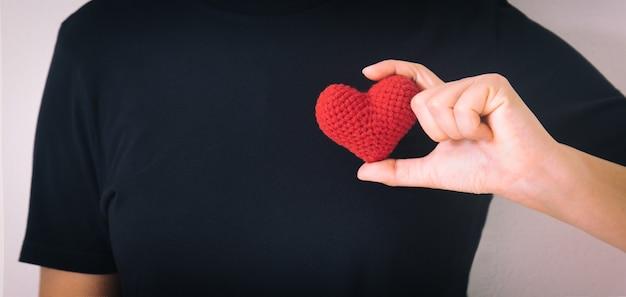 Ręce, trzymając czerwone serce na czarnym tle na białym tle
