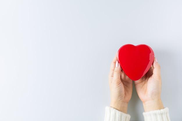 Ręce, trzymając czerwone serce. - opieka zdrowotna, miłość, dawstwo narządów, uważność, dobre samopoczucie, koncepcja. - światowy dzień serca, światowy dzień zdrowia, krajowy dzień dawcy narządów.