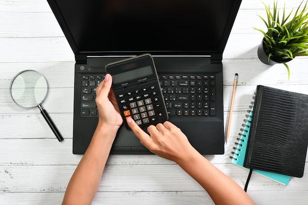 Ręce trzymając kalkulator nad laptopem