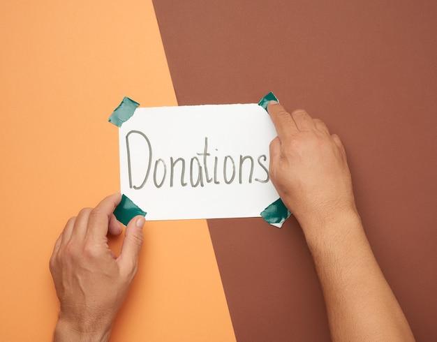 Ręce trzymając kartkę papieru z napisem darowizn