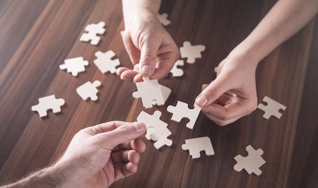 Ręce, trzymając kawałek układanki. rozwiązanie, sukces, praca zespołowa