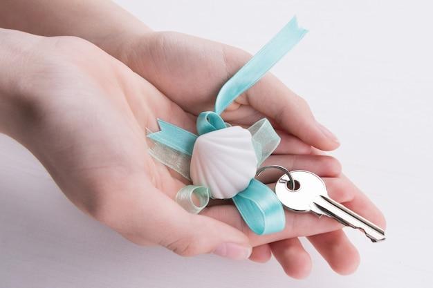 Ręce, trzymając klucze z niebieską wstążką i muszla