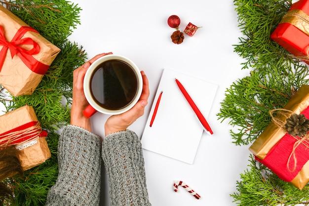 Ręce, trzymając kubek kawy na tle bożego narodzenia
