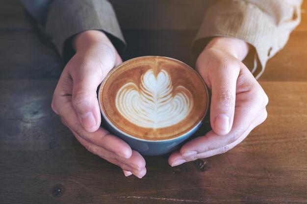 Ręce trzymając niebieski kubek gorącej kawy latte ze sztuką latte na drewnianym stole w kawiarni