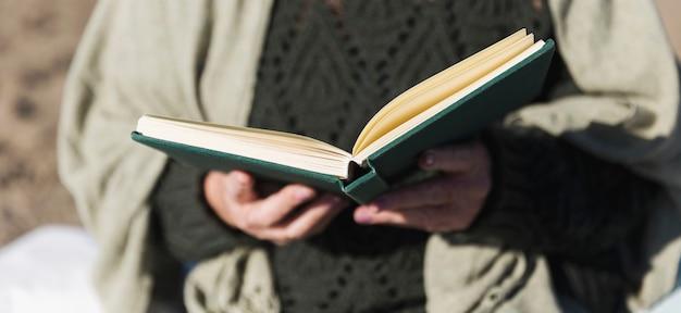 Ręce, trzymając otwartą książkę