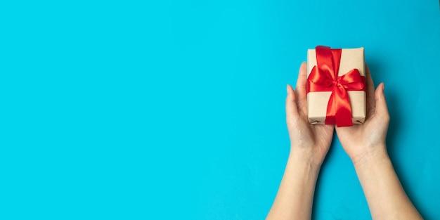 Ręce trzymając papier rzemiosła owinięte pudełko w opakowaniu z czerwoną wstążką